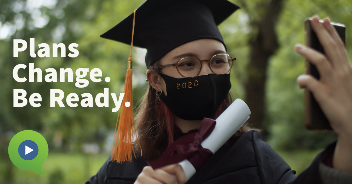 Young graduate holding diploma and phone while wearing a cloth face mask.